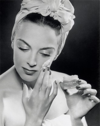 Woman applying skin cream, 1945-1955.