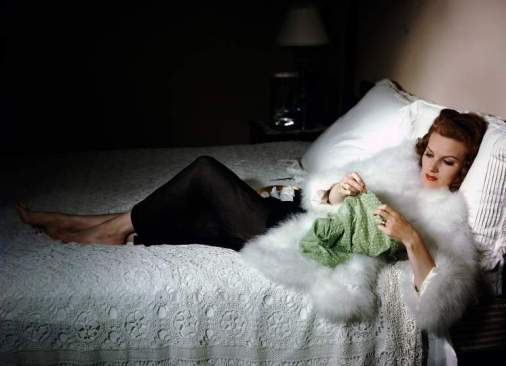 Actress Maureen O'Hara at her home reclining in bed while sewing.