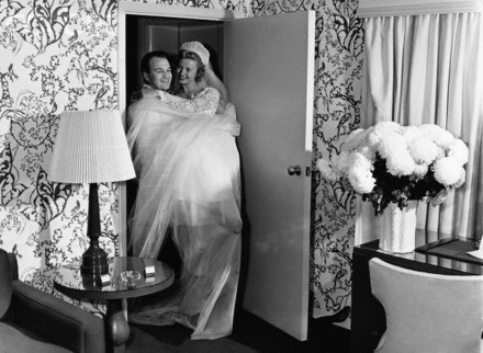 ca. 1950 --- A newly married man carries his bride over the threshold of their new home. --- Image by © Hulton-Deutsch Collection/CORBIS